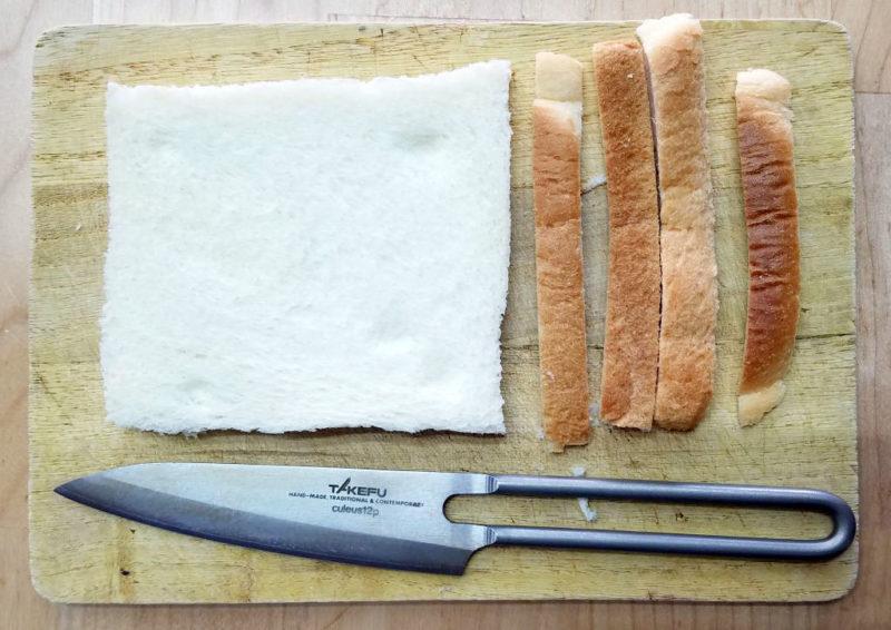 パンの耳を包丁で切る